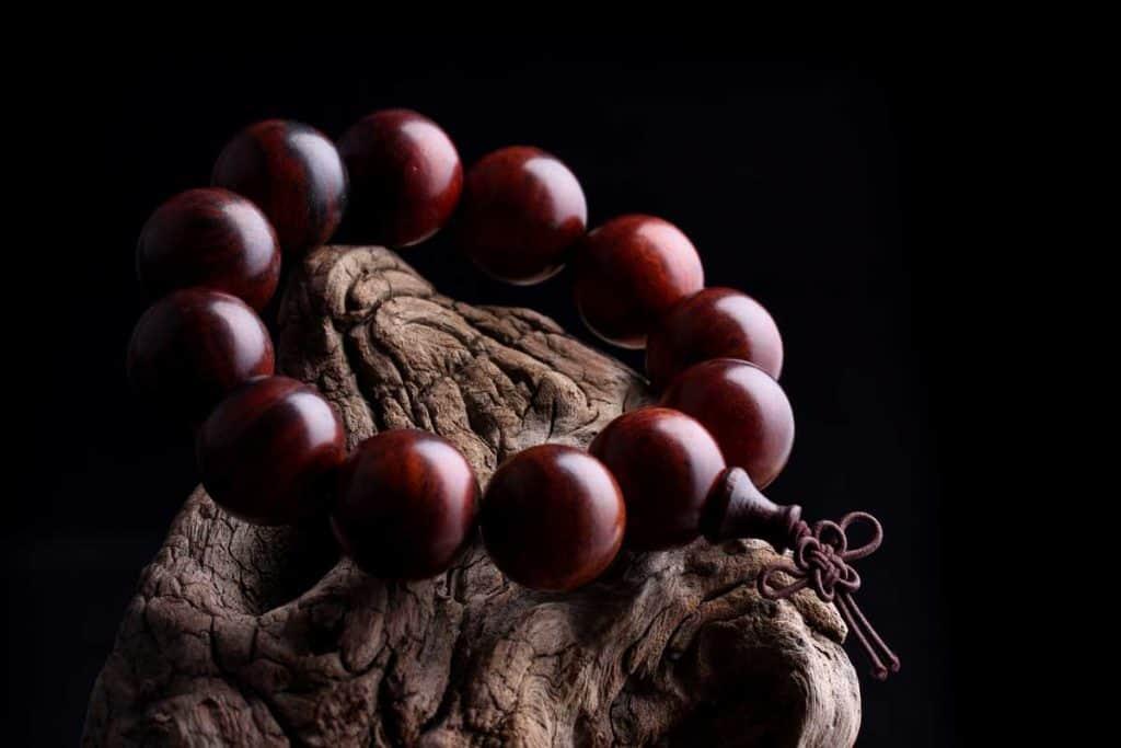 Lobular wooden bracelet placed at wooden holder and black background