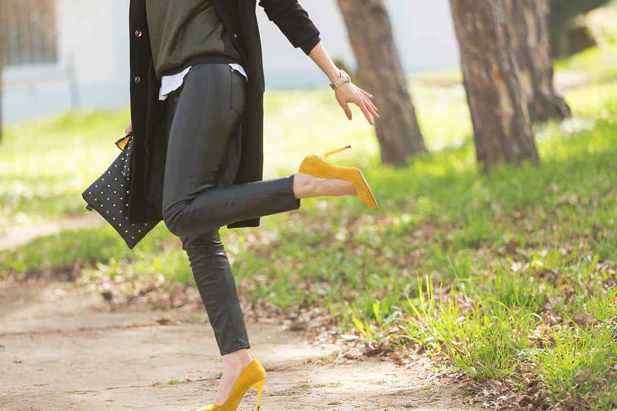 Lower body of a woman in casual attire wearing yellow heels