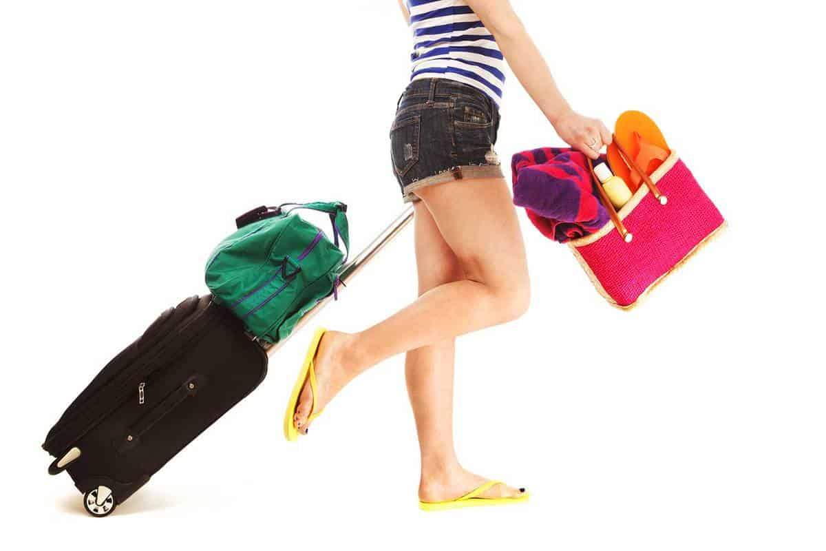 Lower body of a young woman on yellow slippers pulling a roller suitcase with carry-on bag and pink beach bag filled with towel, lotion and other beach gear