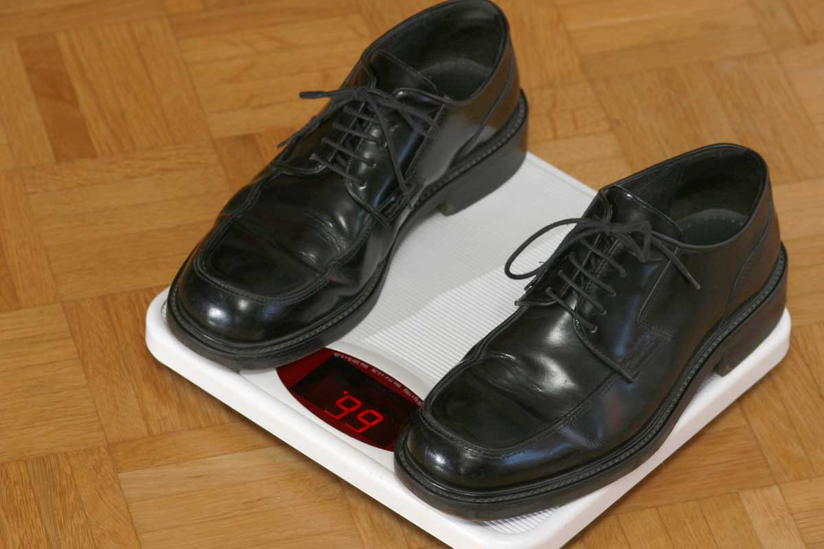 Pair of black shoes on a weighing scale