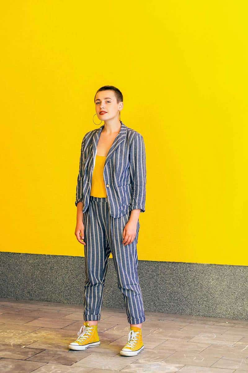 Short hair beautiful woman in yellow shirt, yellow high top sneakers and casual style striped suit