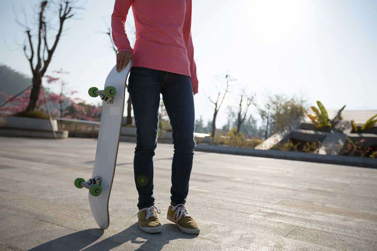 Skateboarder wearing tight blue jeans and sneakers