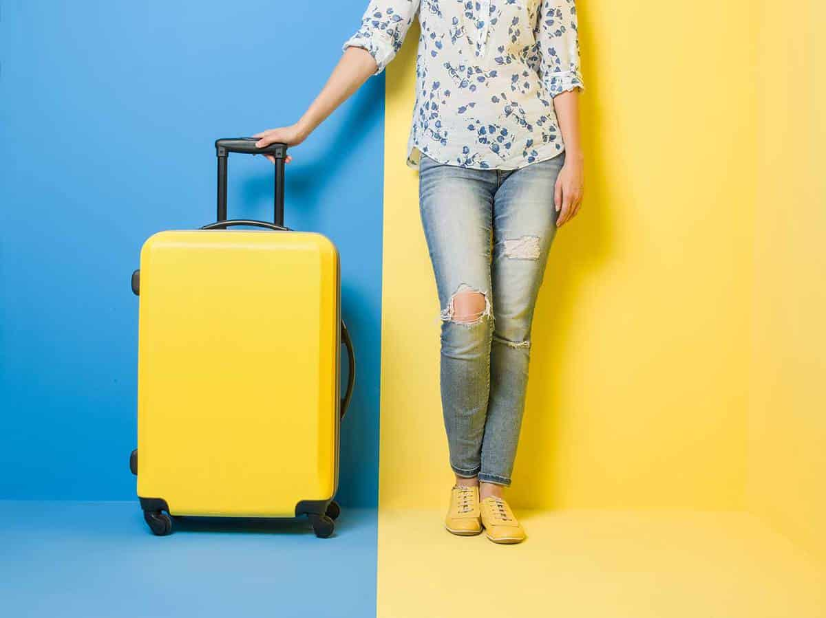 Woman on jeans and yellow shoes stands beside suitcase on colored background