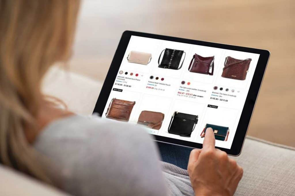 Blonde woman shopping and checking handbags online using a tablet