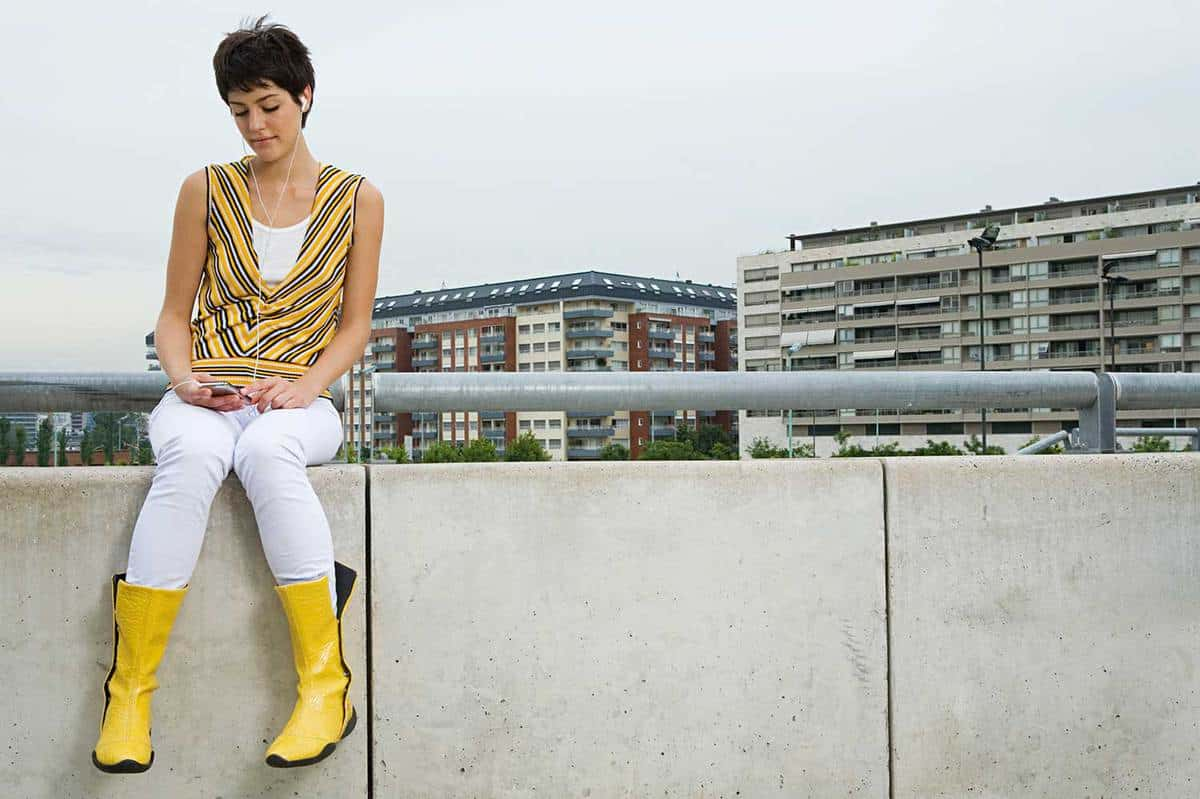 Young woman on yellow boots listening to music