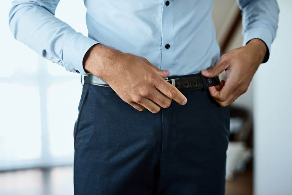 A formal business man putting on his belt, How Many Belts Do You Need?