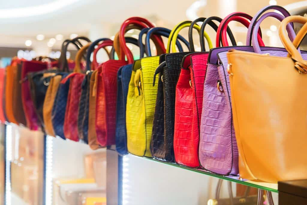 Assorted hand bags stored on a glass cabinet, Where and How to Store Handbags [6 Actionable Suggestions]