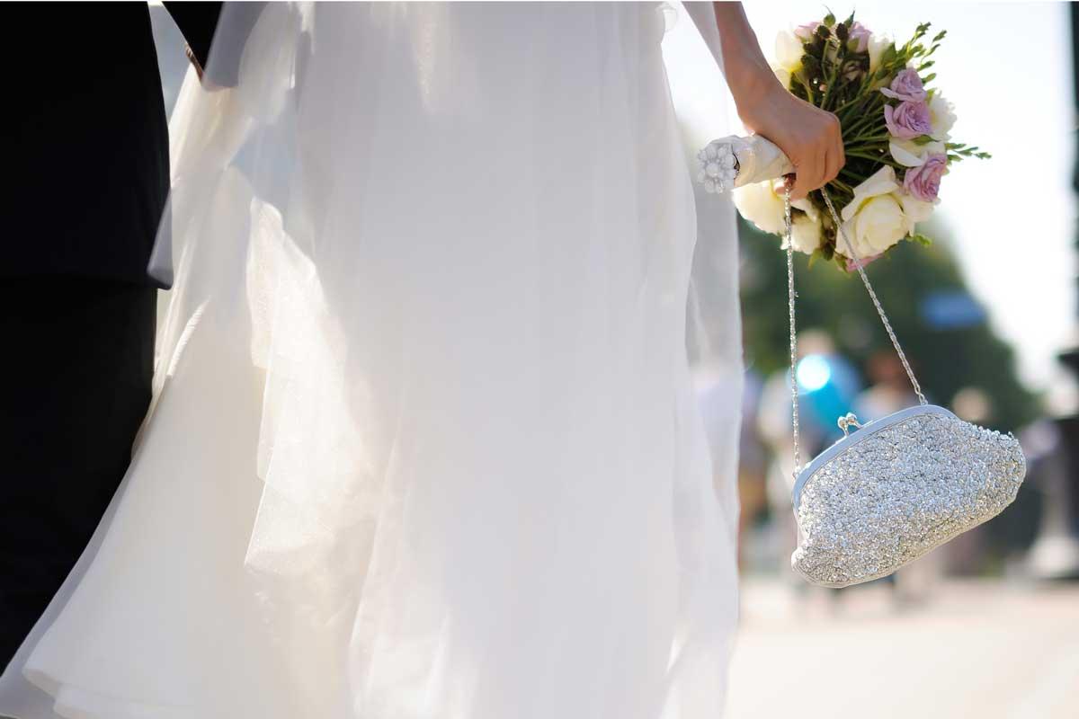 Bride holding a handbag with groom walking across the street, Should A Bride Have A Handbag?