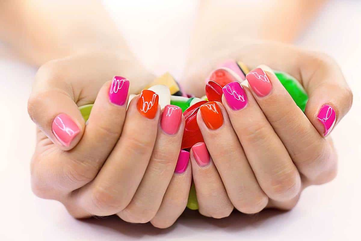 Candies in hands with pink and red nail polish