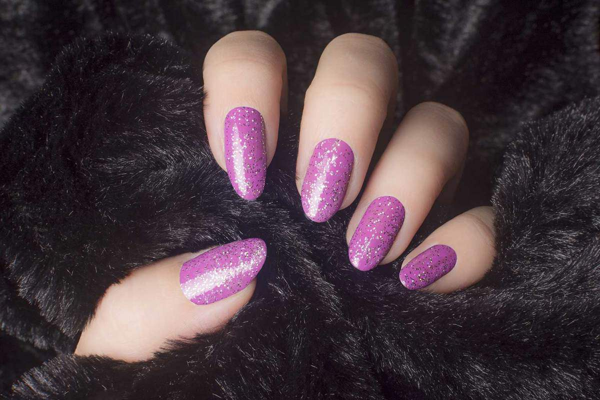 Female hand with glittered pink nails is holding black fur