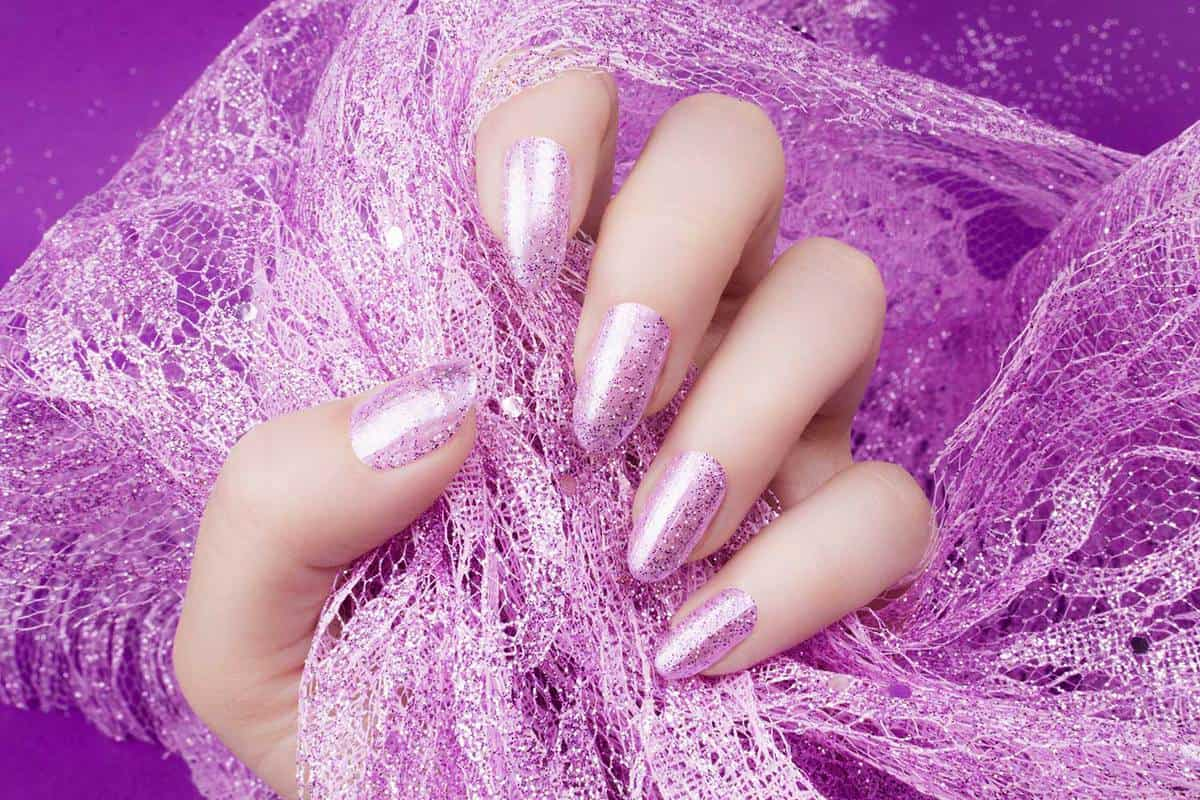 Female hand with glittered pink nails manicure is holding pink decoration on pink background