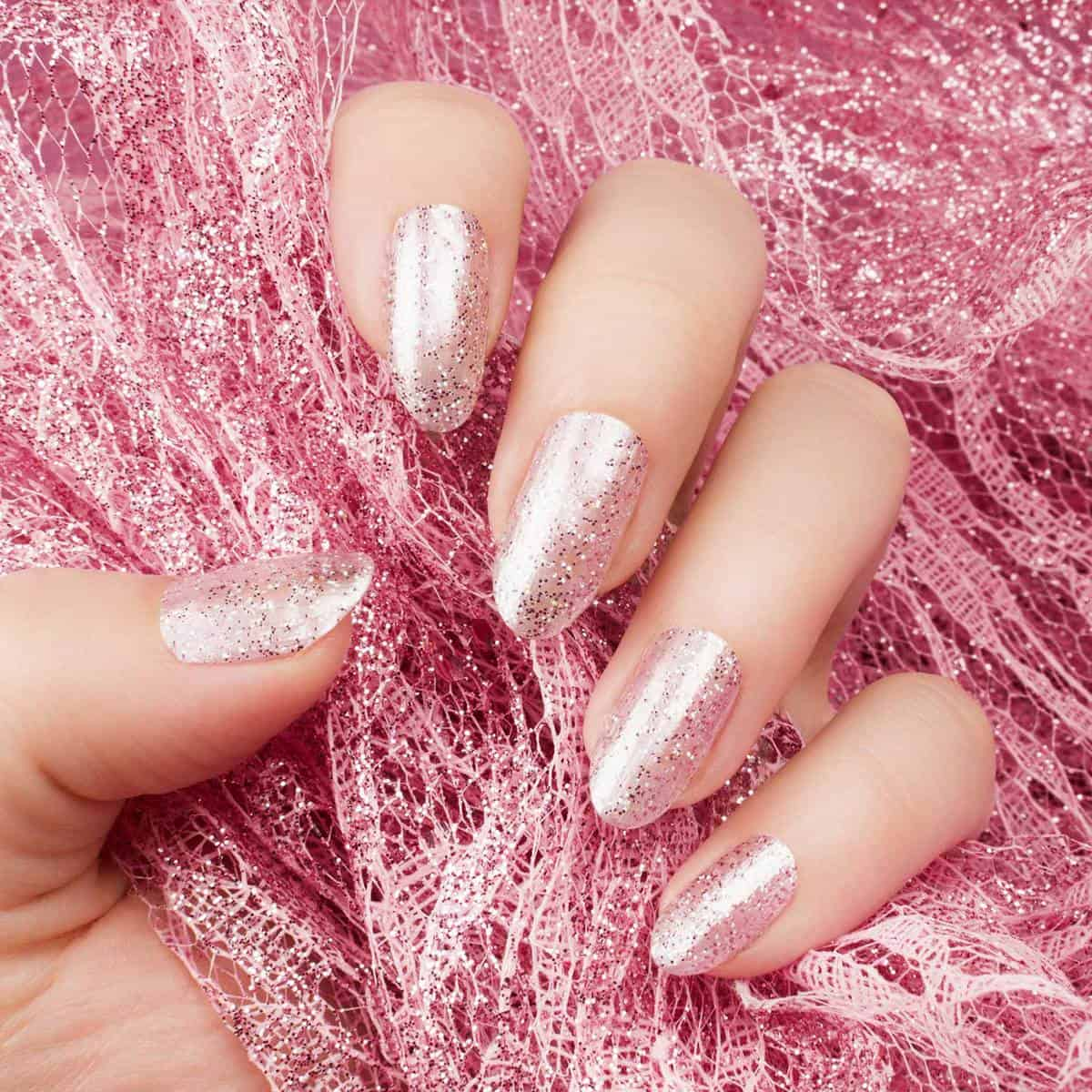 Female hand with glittered shiny rose nails is holding a glittered rose lace
