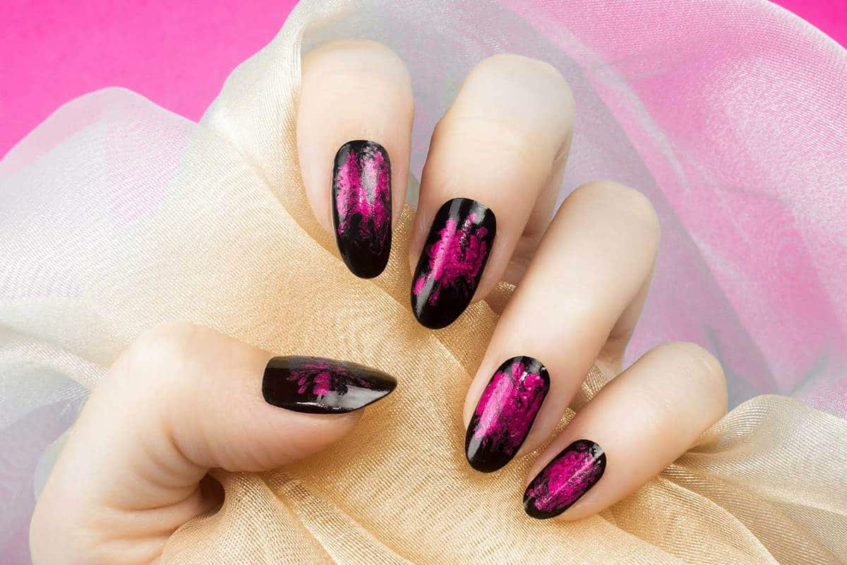 Female hand with pink black nails is holding beige textile on pink background