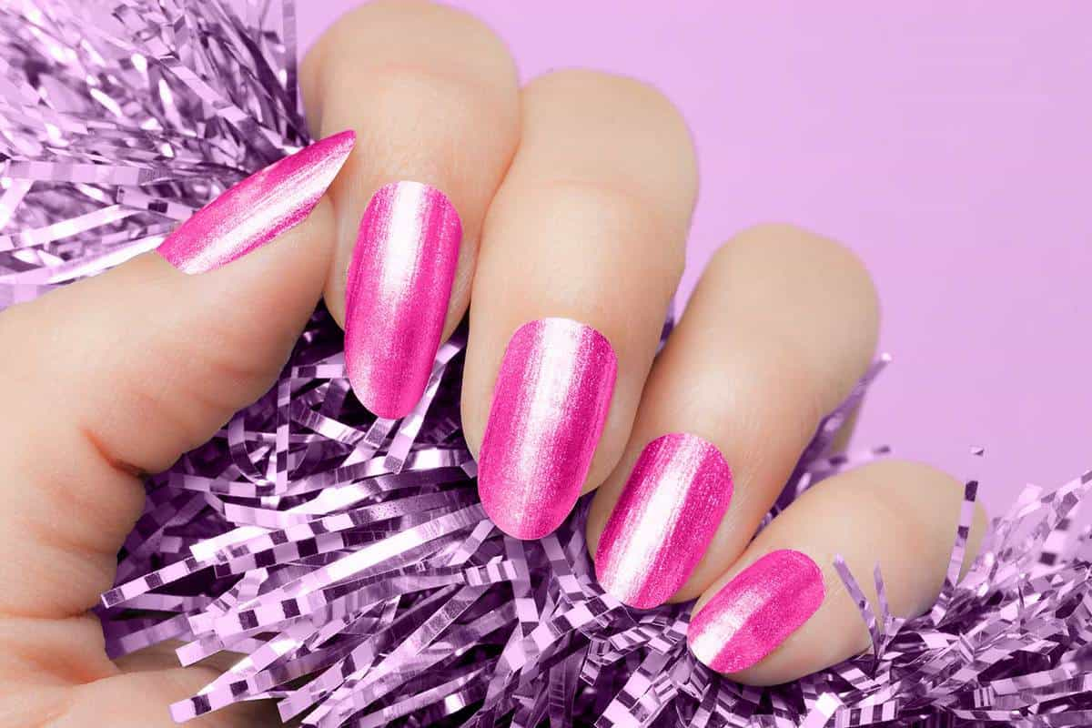 Female hand with pink nails hold purple textured decoration on purple background