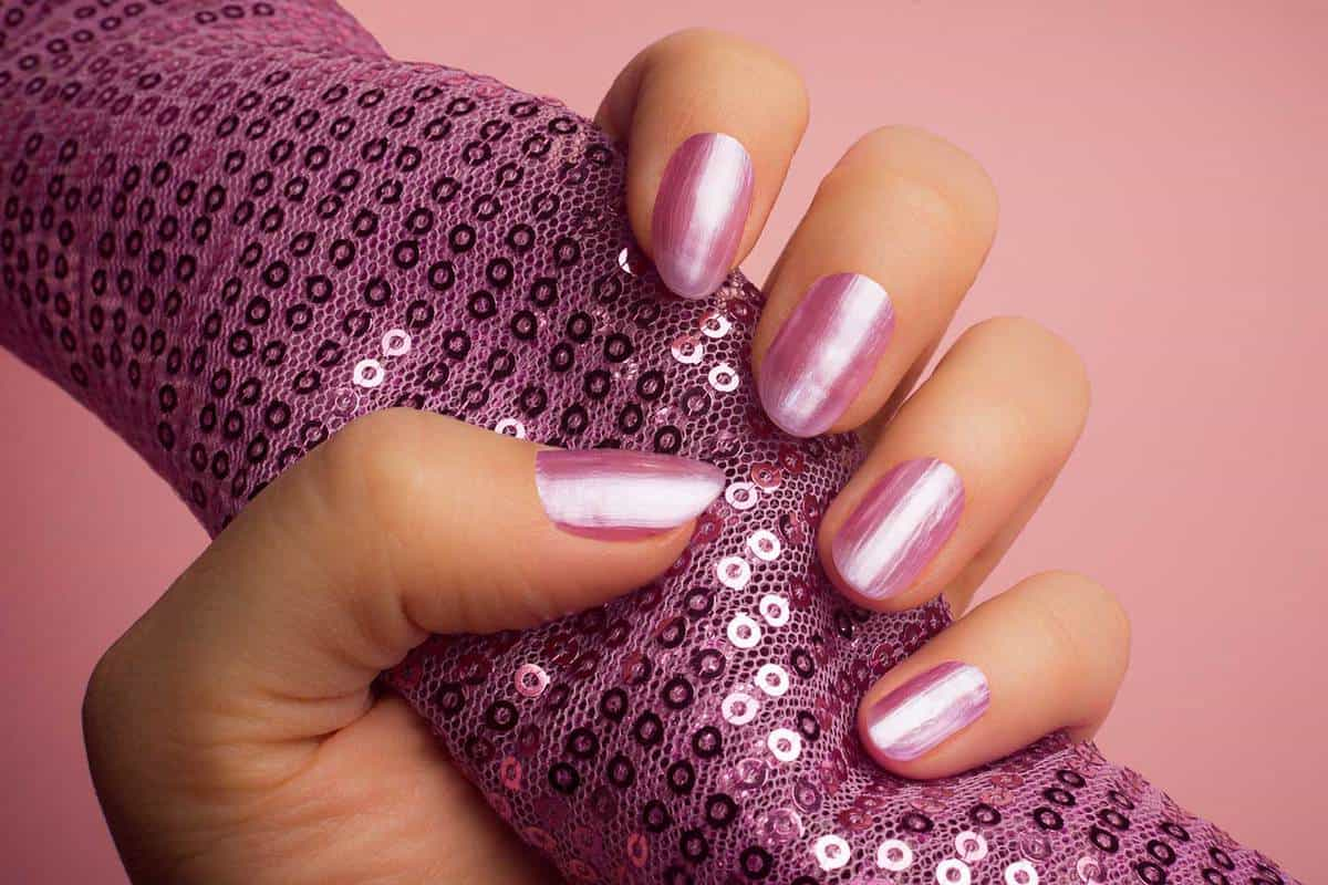 Female hand with shiny pink nails is holding a pink textile with pink glitters on pink background