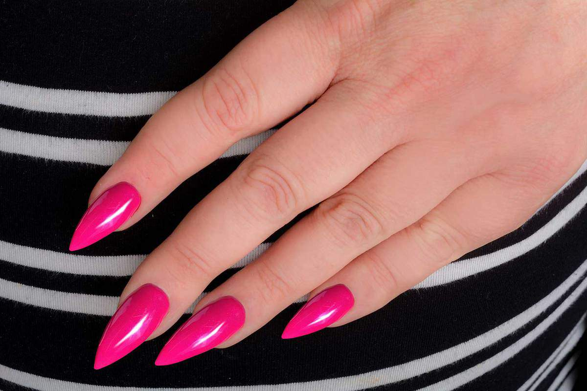 Hand with pink stiletto manicure on striped fabric dress