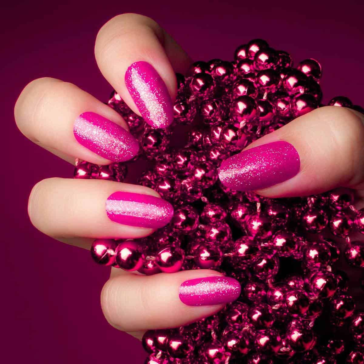 Shiny glittering pink nails with pink pearl jewel on purple background