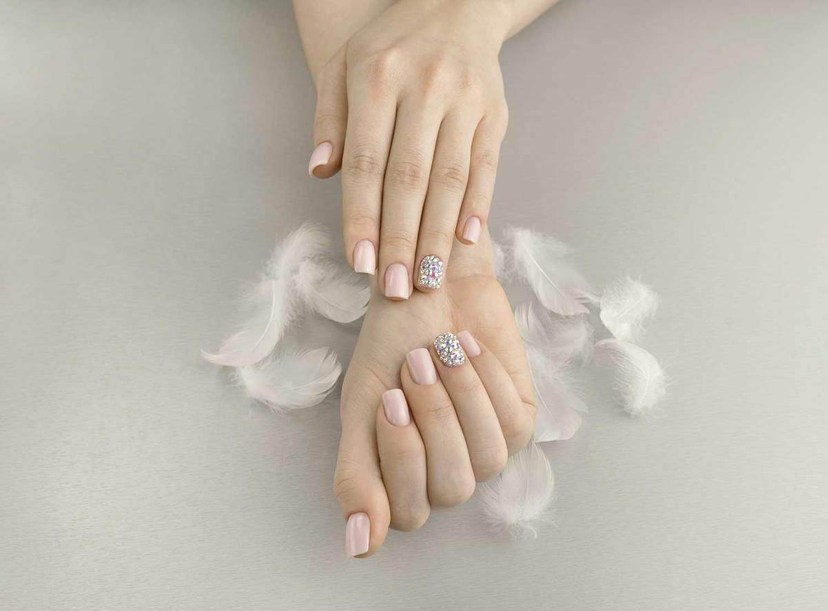 Stylish fashionable women pink manicure with feathers