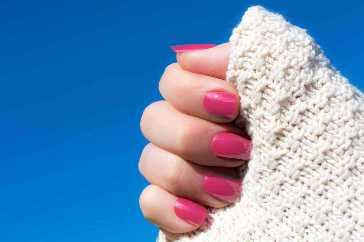 Woman in a white knitted cardigan showing her short pink manicure against blue sky