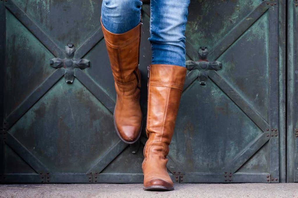 Woman in jeans and brown leather boots leaning on gate, What Are Boots Made Of?