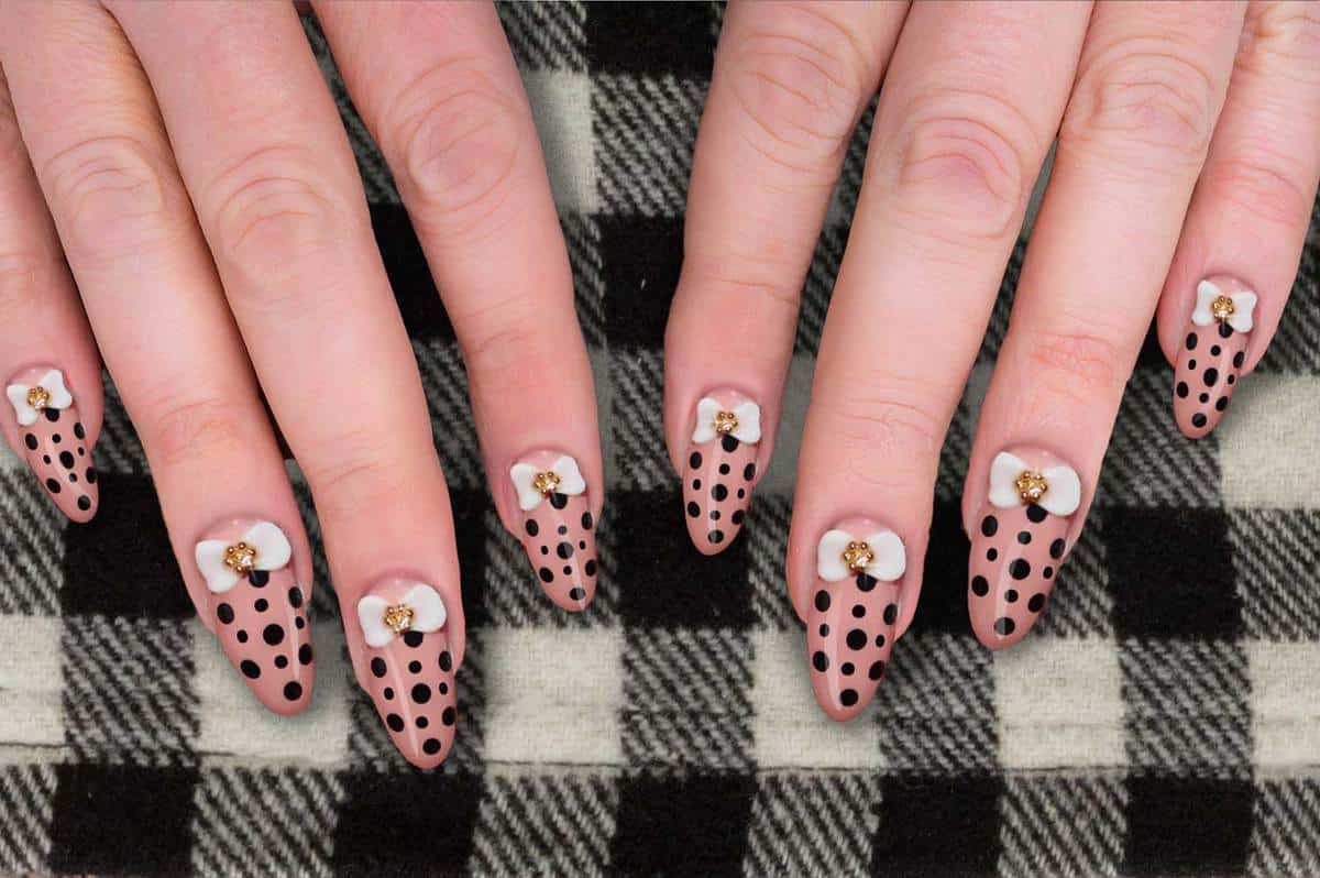 Woman showing her acrylic polkadot pink nails with white bow and rhinestone on checkered woolen skirt