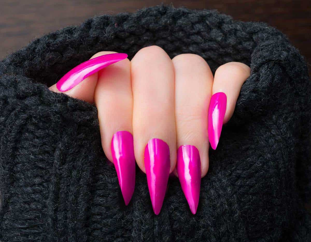 Woman showing her pink stiletto shaped nails in warm cardigan