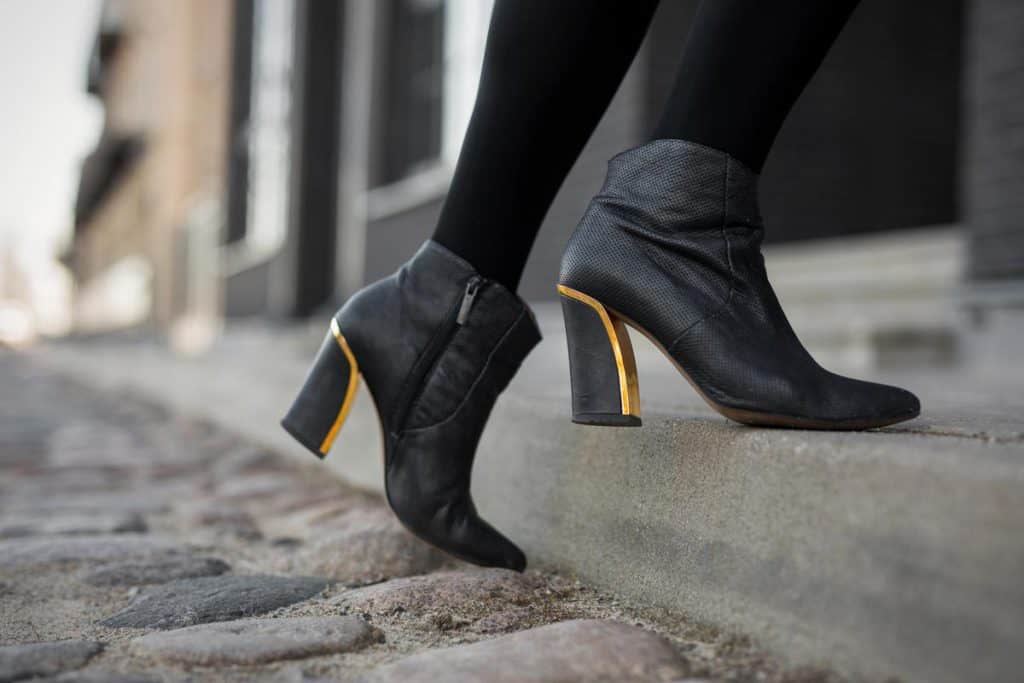 Woman wearing high heeled boots with golden heel plating, 7 Most Comfortable Fashion Boot Brands For Women, Woman wearing high heeled boots with golden heel plating, 7 Most Comfortable Fashion Boot Brands For Women