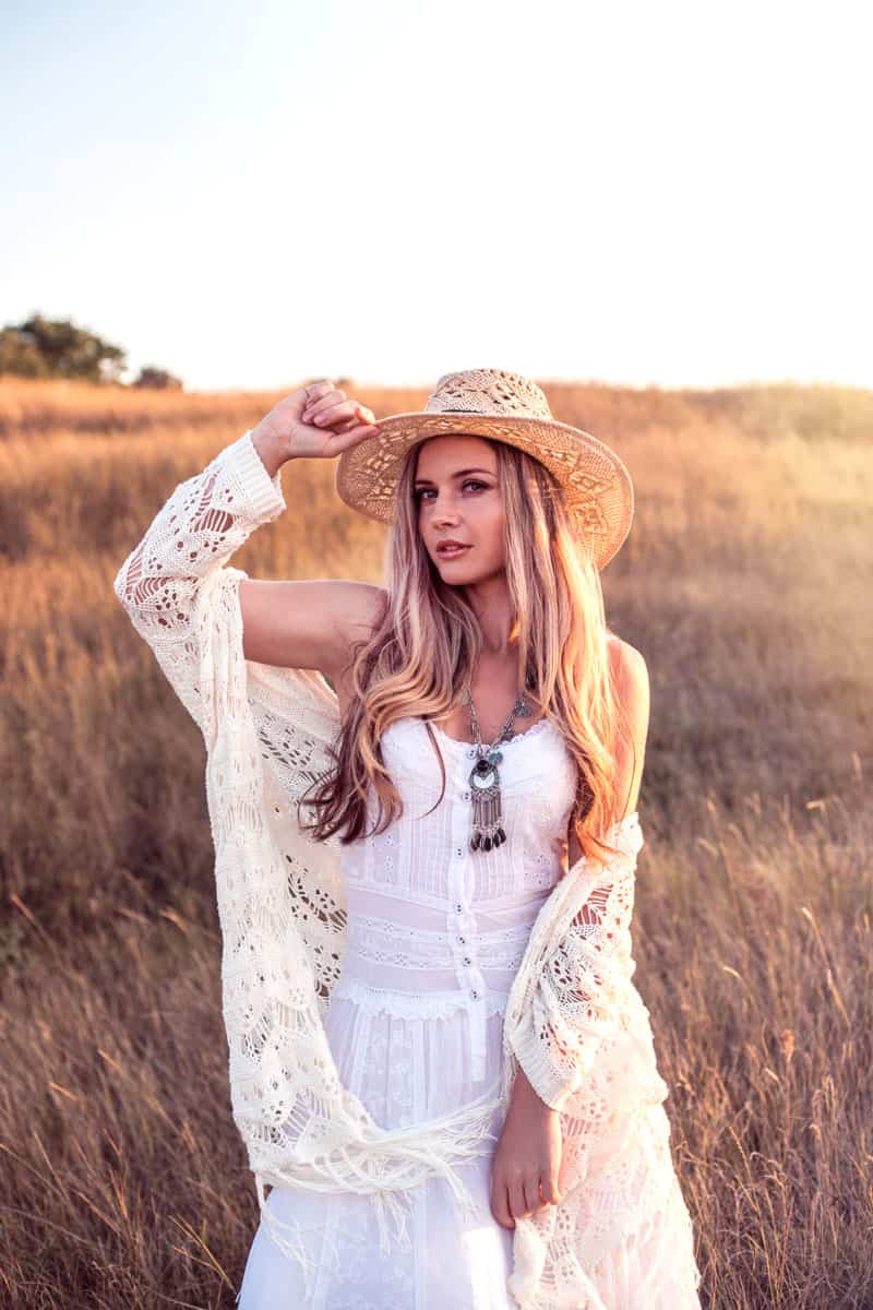 A gorgeous woman wearing an all white dress and a hat while standing on a grassy field