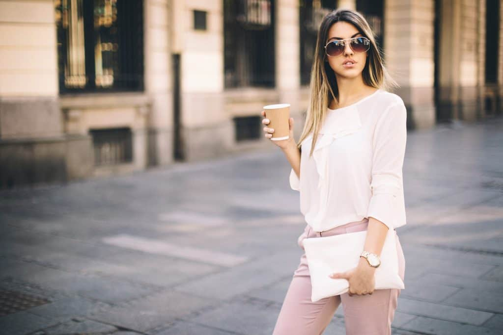 A gorgeous woman with a white shirt and holding her white handbag, How to Wear a White Handbag [9 Suggestions with Pics]