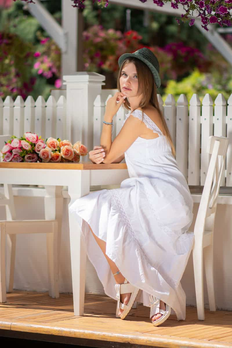 A gorgeous young woman wearing an all white dress and sitting on a chair