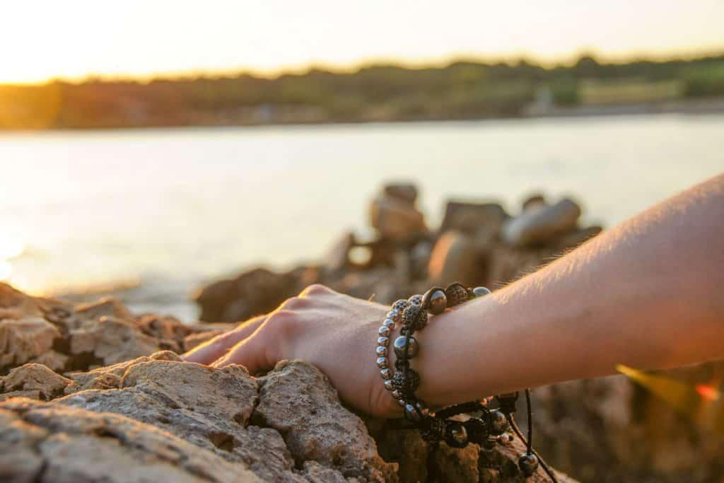 A woman holding a rock exposing her bracelet, Should Bracelets Be Loose?