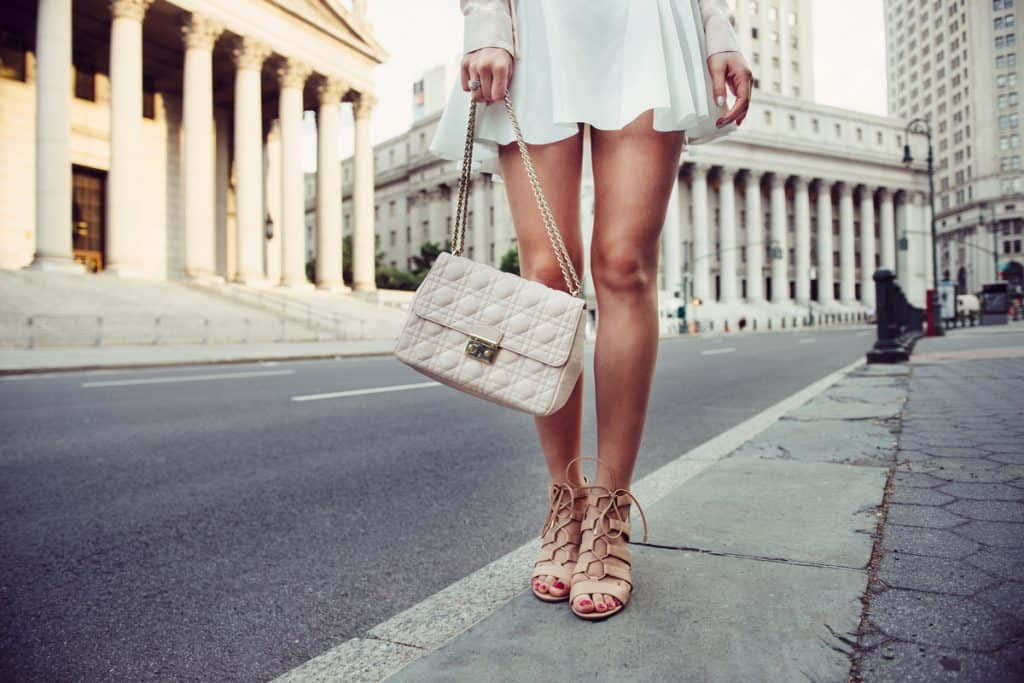 A woman holding her beige colored handbag with her matching sandals while standing on the side of the road