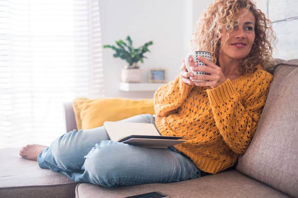 A woman sipping a cup of coffee while wearing her yellow mustard sweater