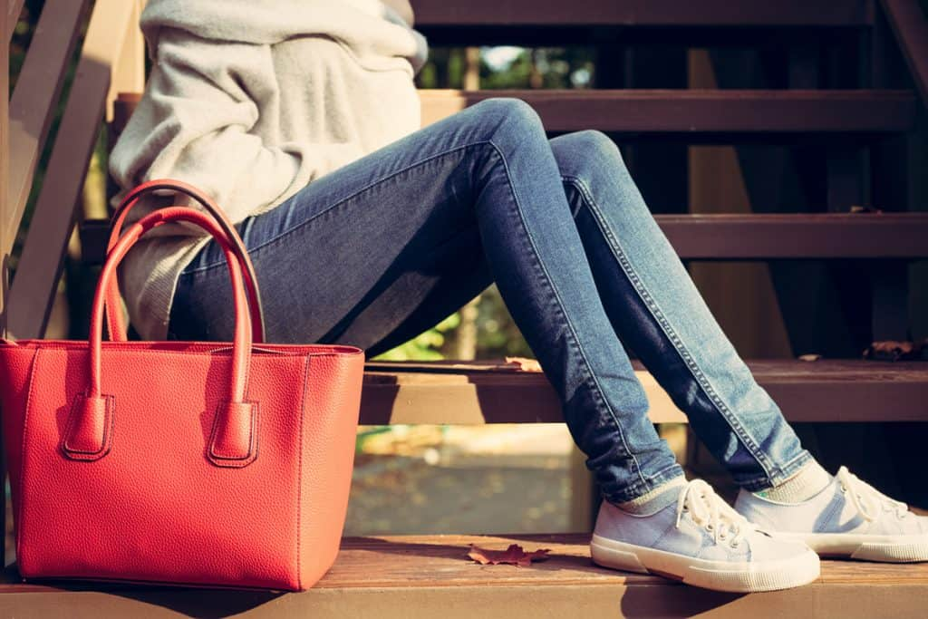A woman sitting on the ground with a red handbag on the side