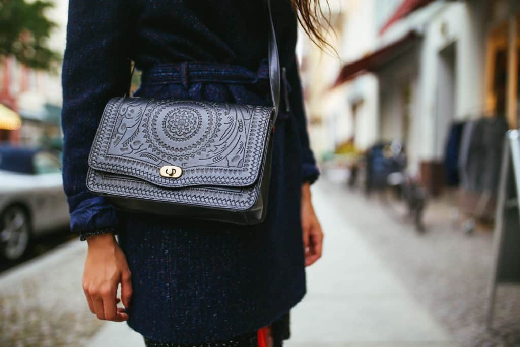A woman wearing a blue dress with a small purse on her side, Where To Buy Handbags [Top 30 Online Stores]