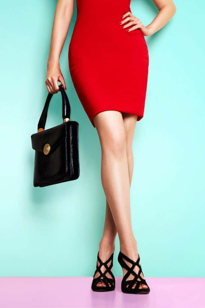 A woman wearing a tight red dress and black shoes holder her black handbag