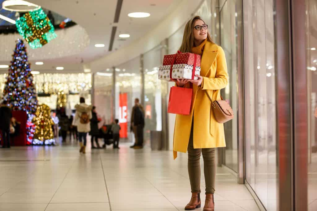 A woman wearing a yellow coat while carrying her Christmas gifts