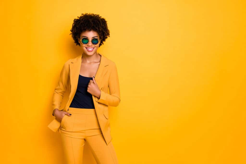A woman wearing a yellow jacket, yellow pants, and a yellow sunglasses while standing on a yellow background