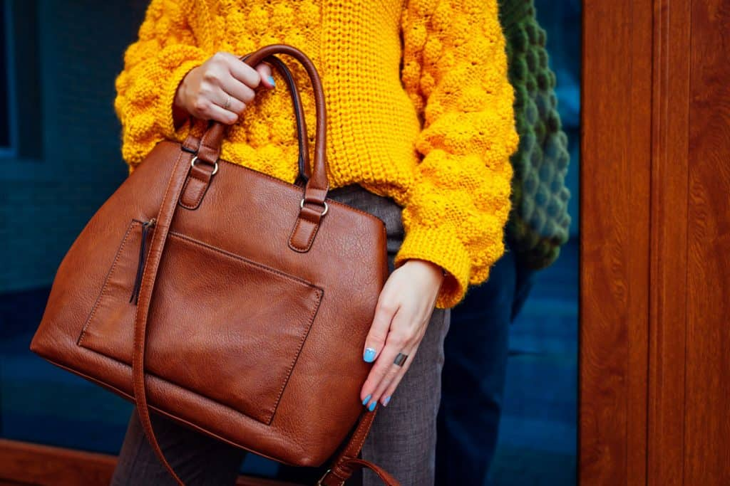 A woman wearing a yellow knitted sweater while carrying her brown leather bag