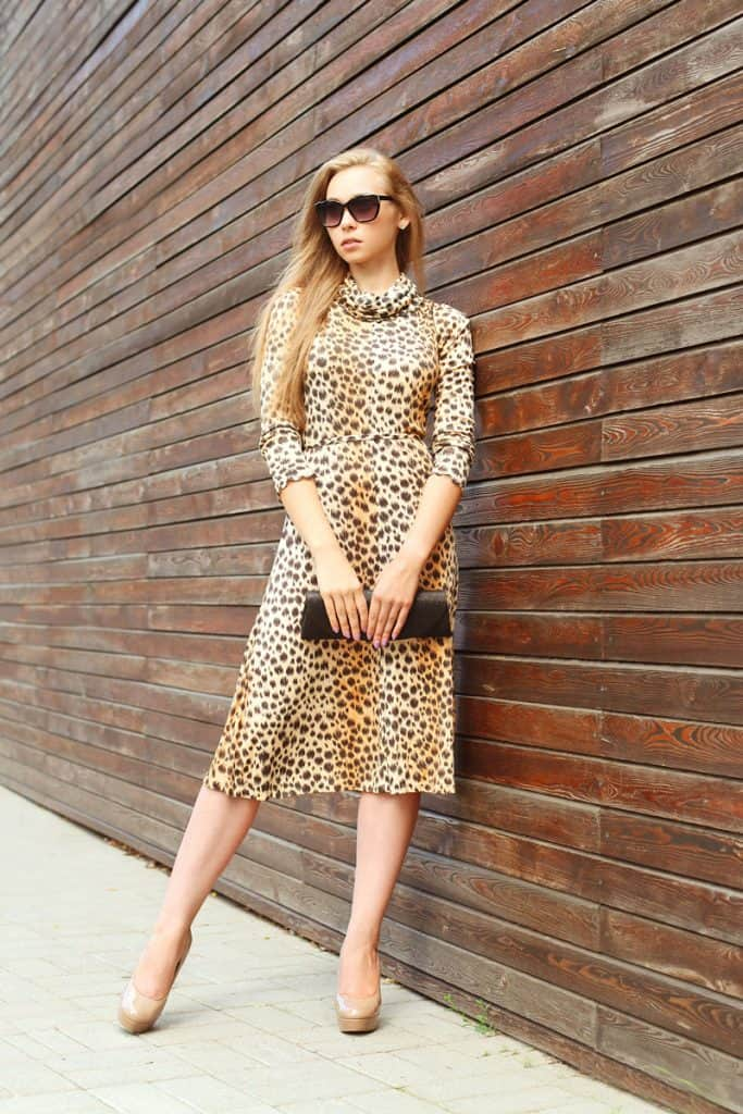 A woman wearing a cheetah skin dress and a light yellow colored shoes holding her black handbag