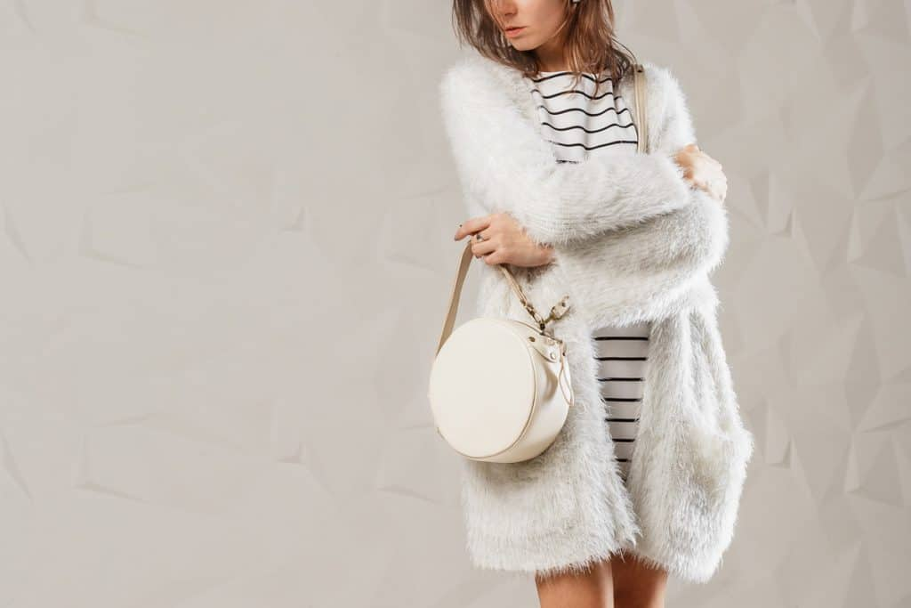 A woman with a white fur coat and holding her white round hand bag, How to wear a white handbag