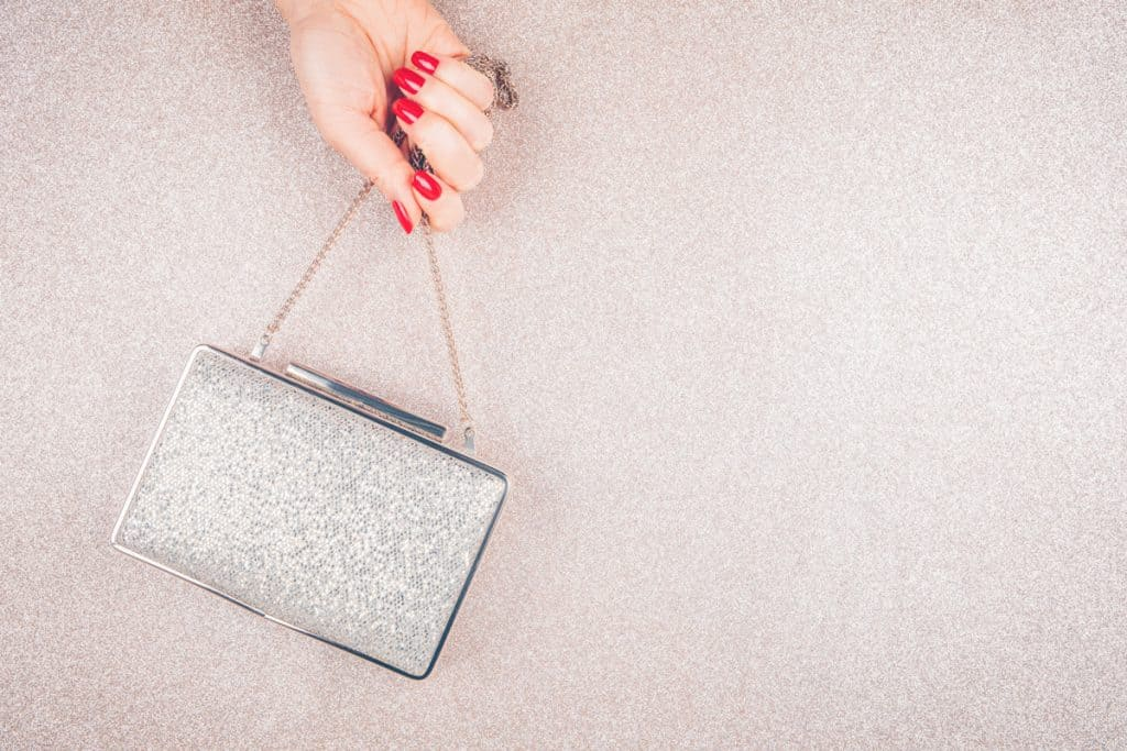 A woman with red colored nails and holding her clutch handbag, Can You Wear a Clutch During the Day?