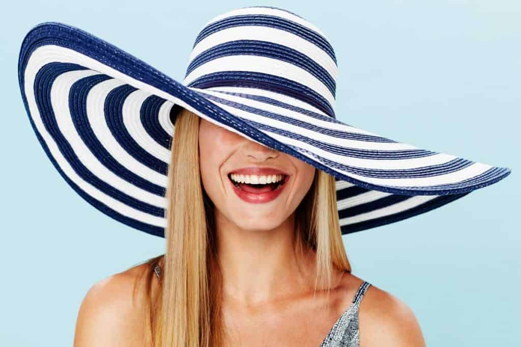 Beautiful blonde woman in striped summer hat smiling, 23 Types Of Hats For Women You Should Know