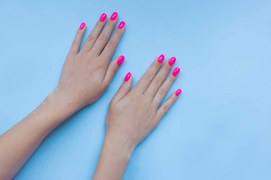 Beautiful neon plastick pink nails on blue background