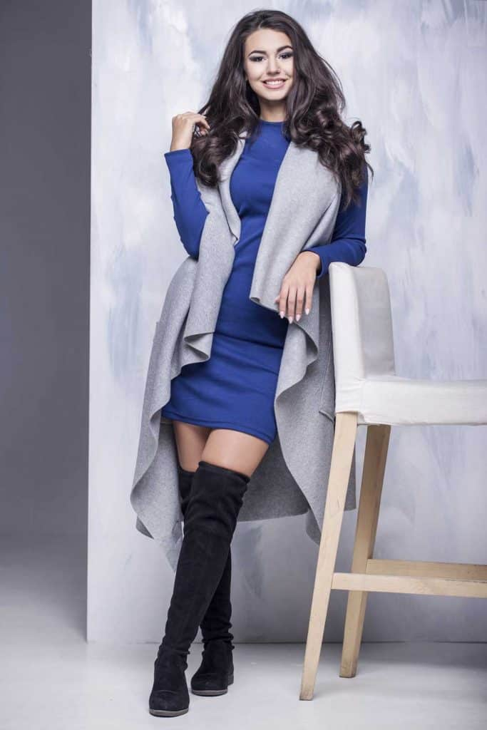 Beautiful young woman in a blue winter dress and a long gray vest