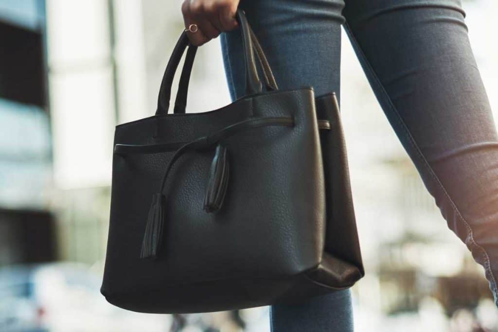 Businesswoman walking with her black handbag in the city, What Color Handbag Goes With EVERYTHING?