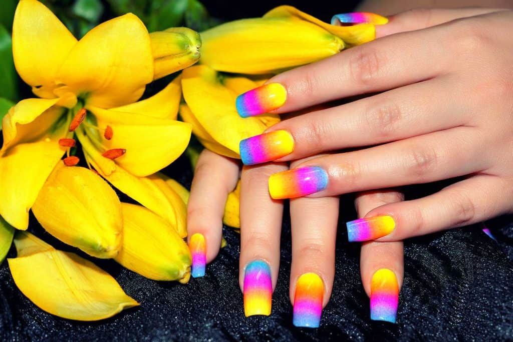 Female hands with colorful nail design holding beautiful yellow flower