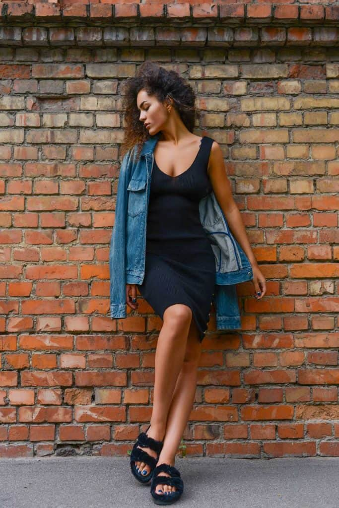 Full-length portrait of young woman wearing black bodycon dress