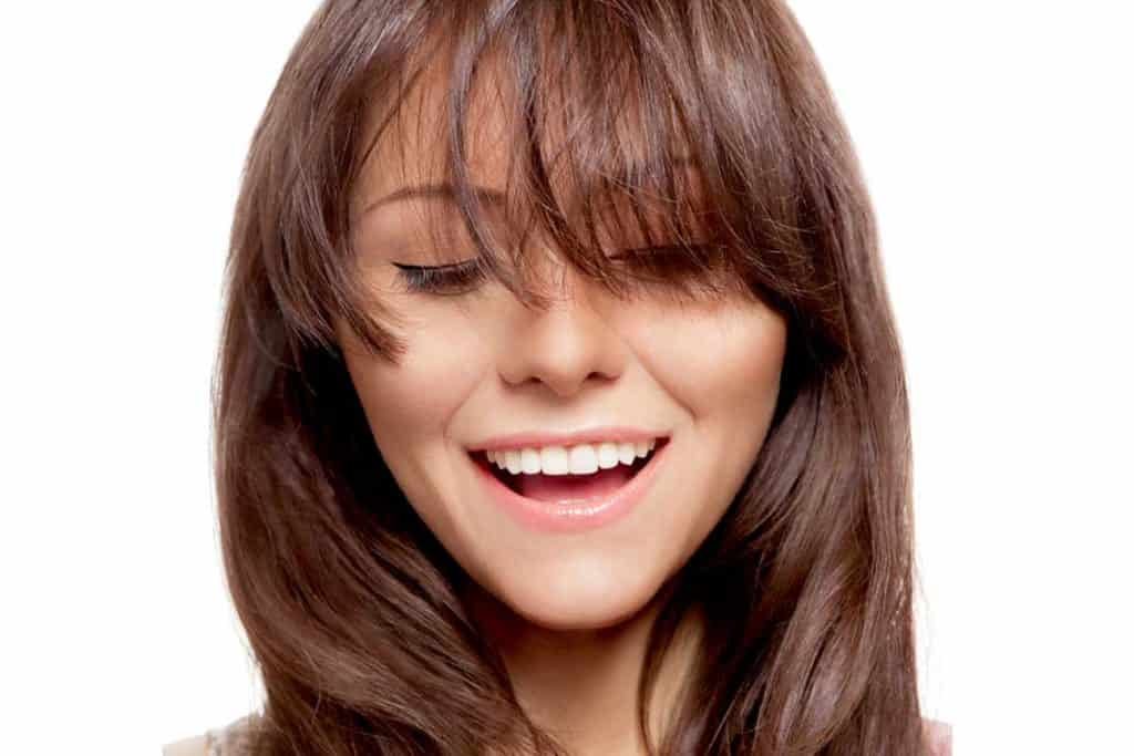 Happy beautiful young brunette with long hair and bangs, Do Bangs Make You Look Older or Younger?
