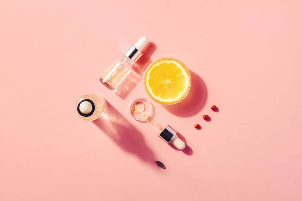 Organic serum with vitamin C placed on a pink surface, How to Use Vitamin C Serum? [Including how when and how often]